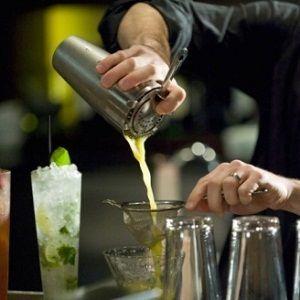 бармен наливає коктейль з шейкера